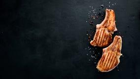 在骨头的牛排用迷迭香 格栅,烤肉 在黑石背景 免版税库存图片