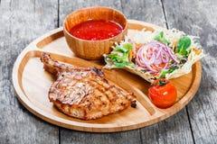 在骨头、新鲜的沙拉、烤菜和西红柿酱的烤牛排在木背景的切板 库存照片