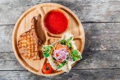 在骨头、新鲜的沙拉、烤菜和西红柿酱的烤牛排在木背景的切板 免版税库存图片