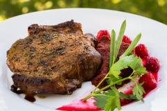 在骨头的油煎的烤猪肉牛排有菜、被捣碎的甜菜根和莓果调味汁的 以叶子为背景 免版税库存图片
