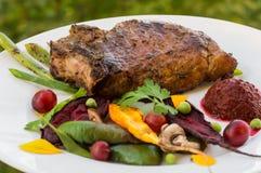 在骨头的油煎的烤猪肉牛排有菜、被捣碎的甜菜根和莓果调味汁的 以叶子为背景 库存照片