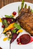 在骨头的油煎的烤猪肉牛排有菜、被捣碎的甜菜根和莓果调味汁的 木背景 顶视图 特写镜头 免版税库存图片