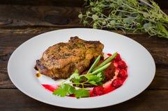 在骨头的油煎的烤猪肉牛排有菜、被捣碎的甜菜根和莓果调味汁的 木背景 顶视图 特写镜头 免版税库存照片