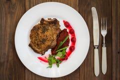 在骨头的油煎的烤猪肉牛排有菜、被捣碎的甜菜根和莓果调味汁的 木背景 顶视图 免版税图库摄影