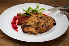 在骨头的油煎的烤猪肉牛排有菜、被捣碎的甜菜根和莓果调味汁的 木背景 顶视图 免版税库存图片