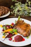在骨头的油煎的烤猪肉牛排有菜、被捣碎的甜菜根和莓果调味汁的 木背景 顶视图 库存照片