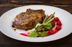 在骨头的油煎的烤猪肉牛排有菜、被捣碎的甜菜根和莓果调味汁的 木背景 顶视图 免版税库存照片