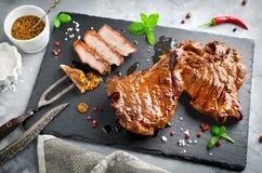 在骨头的烤雕刻在黑s的牛排有刀子的和叉子集合 免版税库存照片