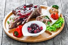 在骨头的烤Ribeye牛排用莓果调味汁、新鲜的沙拉和烤菜在切板在木背景关闭 免版税库存图片