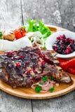 在骨头的烤Ribeye牛排用莓果调味汁、新鲜的沙拉和烤菜在切板在木背景 免版税库存照片