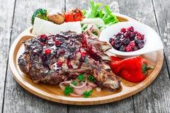 在骨头的烤Ribeye牛排用莓果调味汁、新鲜的沙拉和烤菜在切板在木背景 免版税库存图片