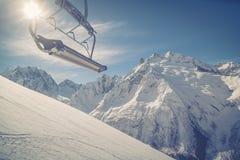 在高加索的雪白山的背景的滑雪吊车导线, Dombai在一个冬天晴天 被定调子的图象 库存照片