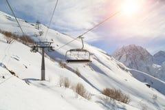 在高加索的雪白山的背景的滑雪吊车导线, Dombai在一个冬天晴天 免版税库存照片