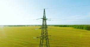 在高压电塔附近的垂直的运动飞行和在绿色和黄色领域的输电线 股票视频