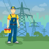 在高压输电线附近的电工人在城市形状背景 免版税库存图片