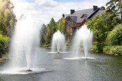 在高喷泉的美丽的景色在豪华豪宅的池塘 免版税图库摄影