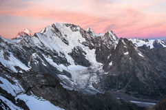 在高多雪的山的日落 库存图片