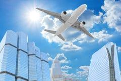 在高大厦摩天大楼上的客机飞行 免版税库存照片