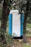 在高大的树木后的便携式的蓝色和白色生态洗手间 免版税库存图片