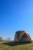 在高小山的绿色围场的一个野营的帐篷反对蓝天的 免版税库存照片