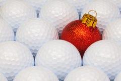 在高尔夫球之间的红色圣诞节装饰 免版税库存照片