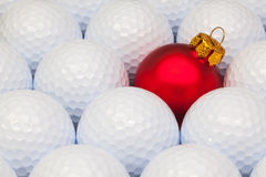 在高尔夫球之间的红色圣诞节装饰 库存照片