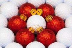 在高尔夫球之间的红色圣诞节装饰 图库摄影