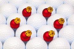 在高尔夫球之间的红色圣诞节装饰 库存图片