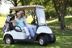 在高尔夫球儿童车的夫妇 免版税库存图片
