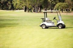 在高尔夫球场的单独高尔夫球儿童车 免版税图库摄影