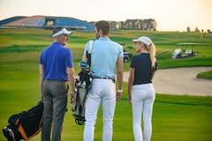 在高尔夫球场的可爱的家庭 免版税图库摄影