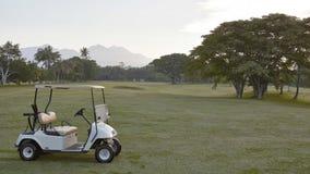 在高尔夫球场的白色儿童车 免版税库存照片