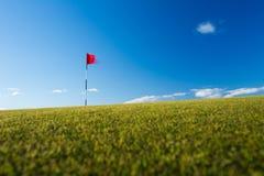 在高尔夫球场的红色高尔夫球旗子 免版税库存图片