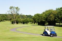 在高尔夫球场的路的高尔夫车 库存照片