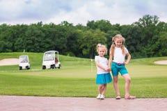 在高尔夫球场的逗人喜爱的一点gilrs 库存照片