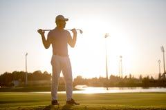 在高尔夫球场的高尔夫球运动员画象日落的 免版税库存图片