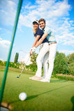 在高尔夫球场的年轻夫妇 库存照片