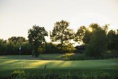 在高尔夫球场的绿色日落的 免版税库存照片