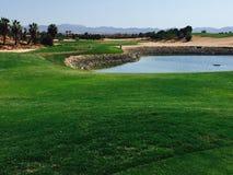 在高尔夫球孔的看法在西班牙以在前面的水危险 免版税库存照片