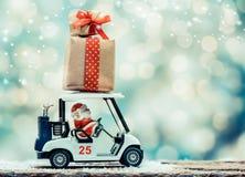 在高尔夫球汽车的圣诞老人有圣诞节礼物盒的 免版税库存图片