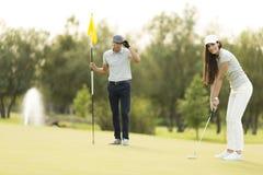 在高尔夫球法院的年轻夫妇 图库摄影