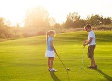 在高尔夫球的孩子调遣拿着高尔夫俱乐部 日落 图库摄影