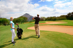 在高尔夫球绿色的夫妇 库存图片