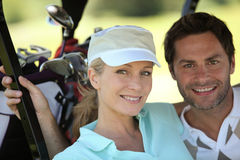 在高尔夫球运动装的夫妇 免版税库存图片