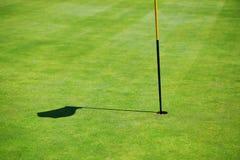 在高尔夫球领域的旗子阴影 免版税库存照片
