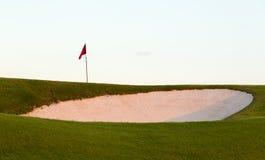 在高尔夫球绿色和旗子前面的沙子地堡 免版税库存照片
