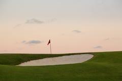 在高尔夫球绿色和旗子前面的沙子地堡 免版税库存图片
