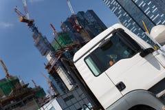 在高层建筑物背景的卡车  免版税库存图片