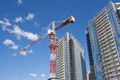 在高层建筑物背景的大厦起重机  免版税图库摄影