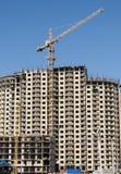 在高层建筑物背景的建筑用起重机  免版税库存图片
